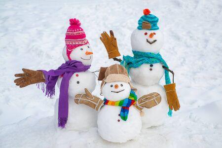 Glückliches Schneemannpaar und Schneemannkind mit dem Weihnachtsgeschenk, das in der Winterweihnachtslandschaft steht. Frohe Weihnachten und ein glückliches Neues Jahr
