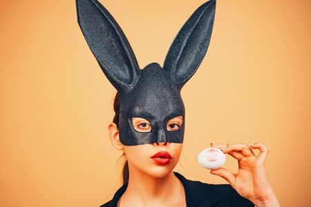 Easter woman. Happy easter. Lips and Easter, Lipstick kiss imprint on easter egg. Bunny woman. Girl with lace bunny ears. Stock Photo - 130851519