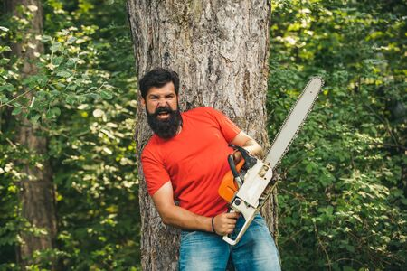 Illegal logging continues today. Lumberjack in the woods with chainsaw axe. Lumberjack on serious face carries chainsaw. Woodcutter with chainsaw on sawmill.