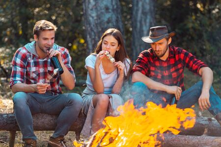 Friends relaxing near campfire after day hiking or gathering mushrooms. Tourism concept. Best friends spend leisure weekend hike barbecue forest nature background.