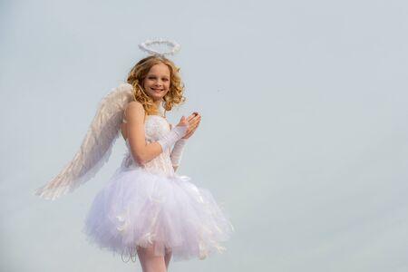 Querubín ángel reza. El Dios del amor. Retrato de niña ángel rubia rizada. Tarjeta de amor. Muchacha del niño del ángel con el pelo rubio rizado - Concepto de la muchacha inocente. Niño con carácter angelical. Foto de archivo