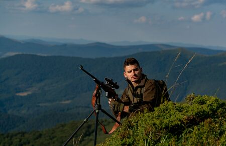 Hunter in camouflage clothes ready to hunt with hunting rifle. Hunting period summer season. Collimating sight. Outdoors active lifestyle.