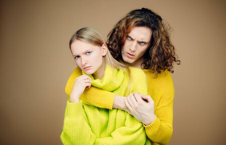 Dissatisfied of young couple hugging. Family conflict discord of two gender concept. Abuse of authority in familie. Young couple having an argument on color background. Relationship problems.