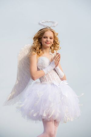 Little goddess with white wings alone on blue sky background. Portrait of a cupid little girl pray. A beautiful teen with blonde curly hair as cupid - Valentines Day. The God of Love. Stock Photo