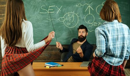Education in high school. Sexology teacher looks at two sexy female students. Erotic education.