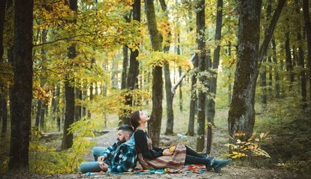 Happy couple on honeymoon vacation travel, romantic getaway dream holidays. Attractive couple having a romantic moment together, dressing in traditional rural style sitting close to each other on an autumn day. The concept love on a date.