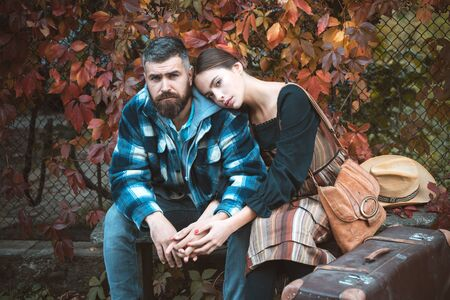 Man and woman in love on a date. Attractive couple having a romantic moment together, dressing in traditional rural style sitting close to each other on an autumn day. The concept of genuine emotions. Meeting and accompany your beloved partner.