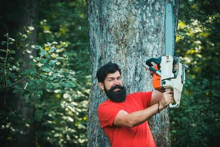 Lumberjack worker with chainsaw in the forest. Lumberjack on serious face carries chainsaw. The Lumberjack working in a forest.