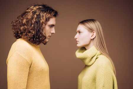 Side view. Curly man and blonde woman facing each other, eyes open. Concept of confrontation in the family. A couple standing face to face with a piercing look. Boyfriend and girlfriend hating each other. 版權商用圖片
