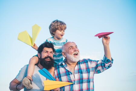 Young boy with father and grandfather enjoying together in park on blue sky background. Grandfather playtime. Happy three generations of men have fun and smiling on blue sky background