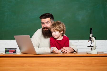 Concept of education and teaching. Preschool pupil. Daddy Teacher. Teacher helping kids with their homework in classroom at school. Chalkboard copy space.