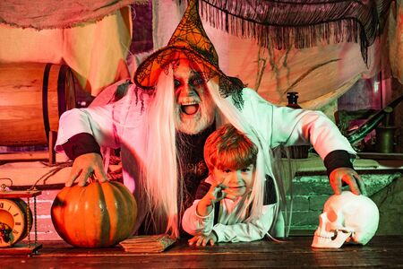 Dad and his kid in carnival costumes on Halloween background. Happy family father and child in costumes on a celebration of Halloween.