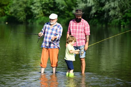 Grandfather, father and boy fishing together. Happy people family have fishing and fun together. Summer day. Outdoors active lifestyle.