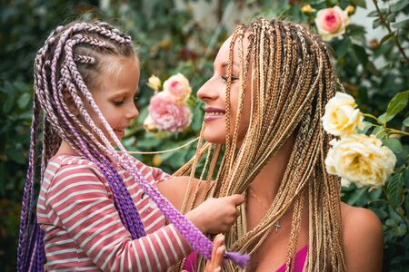 Happy smiling mother with her little daughter with plaits. Hair in trendy weave plait. Lifestyle portrait mom and daughter in happy mood at the outside. Stock Photo