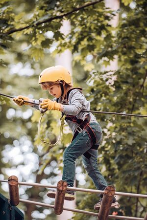Portrait of a beautiful kid on a rope park among trees. Happy child boy calling while climbing high tree and ropes. Eco Resort Activities Stock Photo