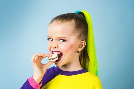 Kid eats macaroon. Elementary schollgirl having a snack breaks with delicacy macaroon. Pastry macaroon. Kid eats tasty macaroon cookies. Sweet meringue-based confection.