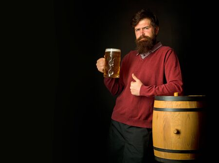 Man holding mug of beer. Happy brewer. Senior man drinking beer with surprise face. Brewery concept. Beer in Germany. Portrait of handsome young man tasting a draft beer. Stock Photo