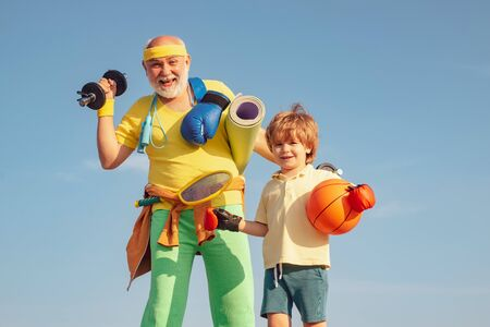 Doing sports is free. Summer sport and fun lifestyle. Be in motion. Grandfather helping child exercising. Active family enjoy sport and fitness. Stok Fotoğraf
