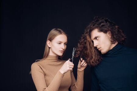 Family crisis. Girl scheming an evil plan of cutting off a curly hair in a man. A smart wily woman has wonderful schemes like a crook of a friend, a dark background. The concept of family betrayal. Revenge of a man for bad intent by cutting his hair.