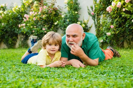 Happy family Grandson hugs his grandpa on holiday. Family summer and active holidays. Grandfather with son in park. Grandson embrace his grandfather.