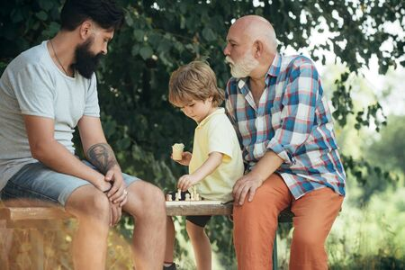 Handsome grandpa and grandson are playing chess while spending time together outdoor. Boy with father and grandfather. Father and son in the park.
