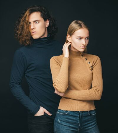 Concentrated girl standing next to a curly boyfriend. Attractive couple together. The beginning of life of a young couple. The first joint family decisions. Warm colors in clothing.