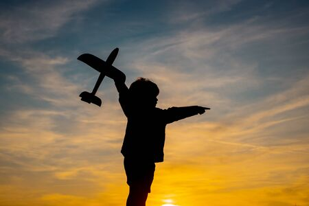 Child playing with toy plane during sunset time in evening. Child playing with model plane. Summer at countryside