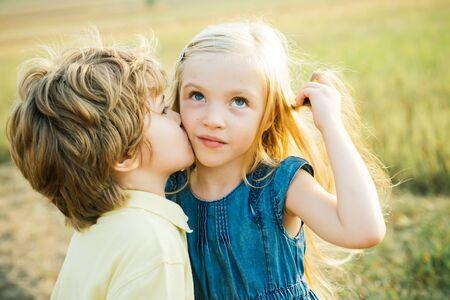 Kids having fun in green field against blue sky background. Festive Art Greeting Card. Lovely children. Little angels in love. Love concept. Valentine. Love story. Stock Photo