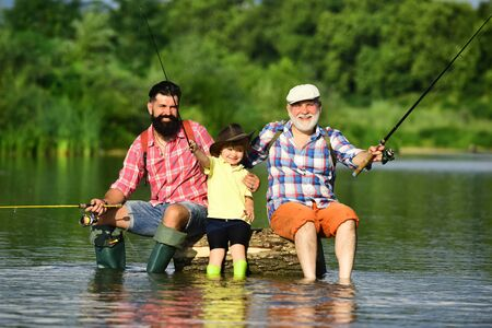 Family fishermen fishing with spinning reel. Summer weekend. Happy grandfather, father and grandson with fishing rods on river berth. Happy weekend concept. Stok Fotoğraf
