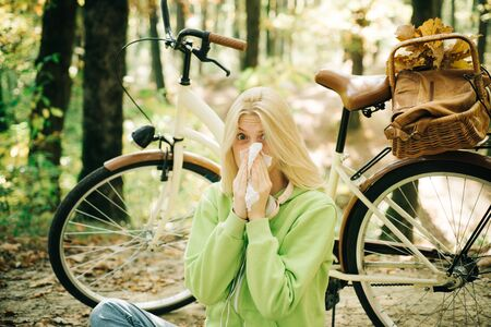 Young blonde in a green sweater sitting on the ground in the park blowing her nose on bicycle background. Seasonal allergy. Woman handkerchief sneezing because of allergy. Blonde allergic reaction relax forest. Girl bicycle in nature. Woman bicycle autumn forest suffers from allergy