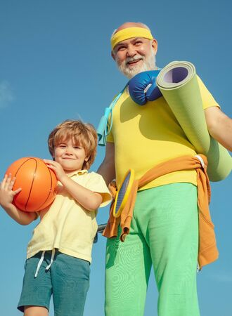 Sports coach and kid with basketball ball. Like sports. Different generations. Outdoor activities and healthy lifestyle. Grandfather giving grandson ride on back in park. Stok Fotoğraf