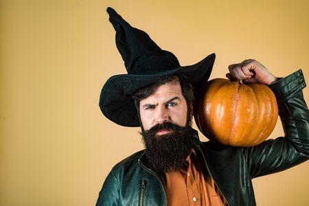 Bärtiger Mann kocht im Halloween-Hut mit Kürbis. Design für Halloween-Banner. Hübscher Halloween-Mann mit Kürbis in der Hand. Das verrückte Jokergesicht. Lächelnder glücklicher Mann mit Kürbis.