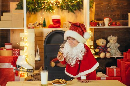 Happy Santa Claus - cute boy child eating a cookie and drinking glass of milk at home Christmas interior. Little Santa picking cookie and glass of milk at home. Stock Photo