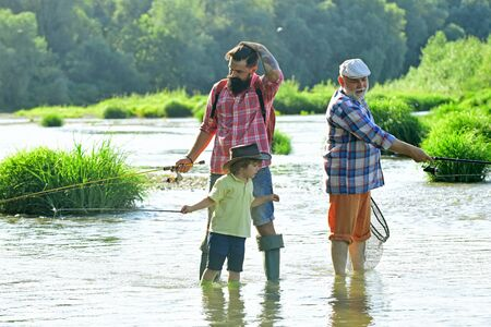 Old and young. Father, son and grandfather relaxing together. Fishing in river. Young - adult concept. Happy fisherman with fishing rod.