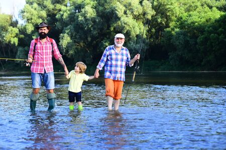 Boy with father and grandfather fly fishing outdoor over river background. Man in different ages. Hobby and sport activity.