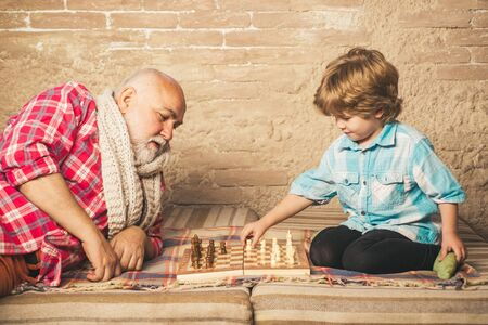 Senior man teaching his grandson to play chess. Handsome grandpa and grandson are playing chess while spending time together at home.