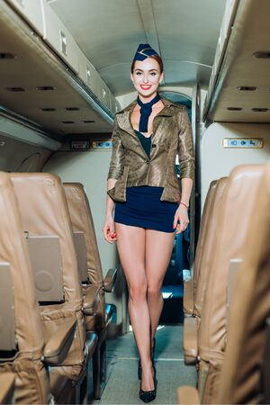 Airline. Cabin crew. Beautiful flight attendant in an airplane smiling. Stewardess and travel time. Flight attendant. Attendant. Profession stewardess.