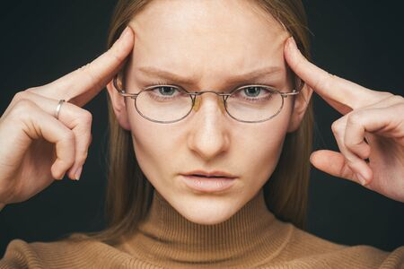 Woman trying keep emotions under control feeling distressed and drained massaging temples with fingers. Trying pull emotions together. Studio shot of displeased unhappy european woman in glasses, opening eyes and holding fingers on temple while suffering migraine or headache, waiting for painkillers. Stock fotó