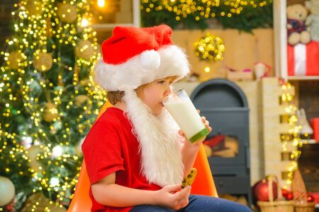Santa boy child eating cookies and drinking milk. Portrait of bearded funny child in Santa costume. Santa fun. Santa Claus eating cookies and drinking milk on Christmas Eve