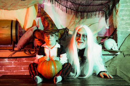 Family party on Halloween. Grandpa and grandson with pumpkin together as preparation for Halloween. Dad and his kid in carnival costumes on Halloween background. Stok Fotoğraf