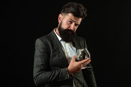 Handsome bearded businessman is drinking expensive whisky. Sommelier man. Man with beard holds glass of brandy. Imagens