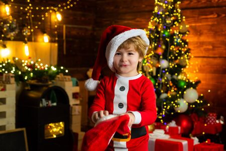 Kid boy santa hold christmas gift red sock. Childhood moments. Child cheerful face got gift in christmas sock. Check contents of christmas stocking. Joy and happiness. Christmas stocking concept 版權商用圖片