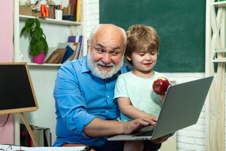 Grandfather talking to grandson. Learning and education concept. Concept of a retirement age. Grandfather and grandson. Cute little preschool kid boy with Grandfather in a classroom. Stok Fotoğraf