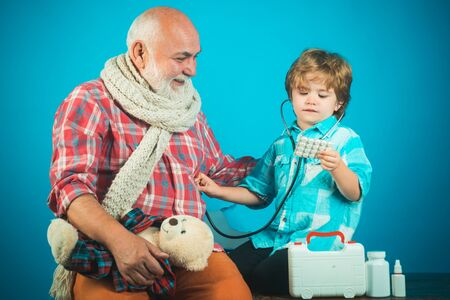 Family playing in doctor and patient. Childhood. Kid play doctor with dad on color background. Medicine age and health care concept. Stok Fotoğraf