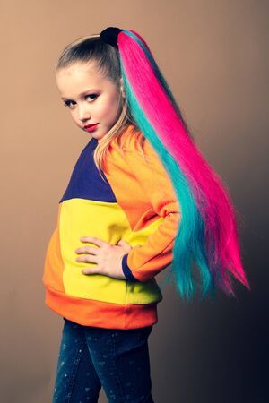 Colorful makeup and rainbow hair. Fashion photo of gorgeous European little model with art design. Studio shot of kid girl looking on camera, isolated on color background. 写真素材