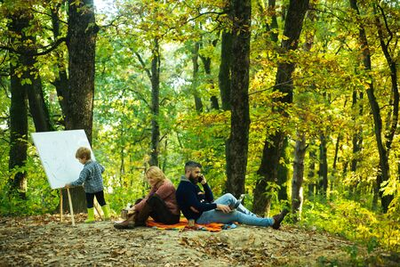 Alternative workday. Handsome son drawing family giving joyful moments to mom and dad. Parents working using laptop and phone. Family day, family activities in nature. Ecology lesson. Forest preschool and ecology education. Stock Photo