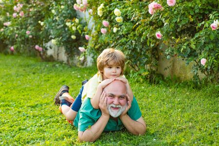 Happy loving family. Two different generations ages: grandfather and grandson together. Grandpa retiree. Grandfather with son in park. Father and grandfather. Grandson embrace his grandfather. Standard-Bild - 131526576