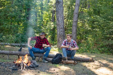 Young man having picnic in woods. Camp adventure and travel concept. Happy friends enjoying bonfire in nature. Group of two male friends camping with marshmallows over a camp fire. Banco de Imagens