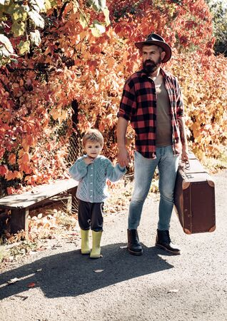 Father with suitcase and his son. Bearded dad telling son about travelling. Traveler with lot experience. Spirit of adventurism. Family time. Adventure with son. Telling stories about past times Stock Photo
