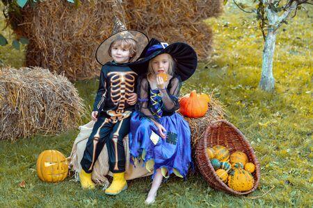 Cute children wearing Halloween costumes having fun on Halloween celebration. Halloween party with children wearing Halloween costumes.